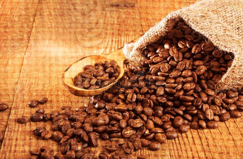 在小大袋的烤咖啡豆在木桌上 库存图片