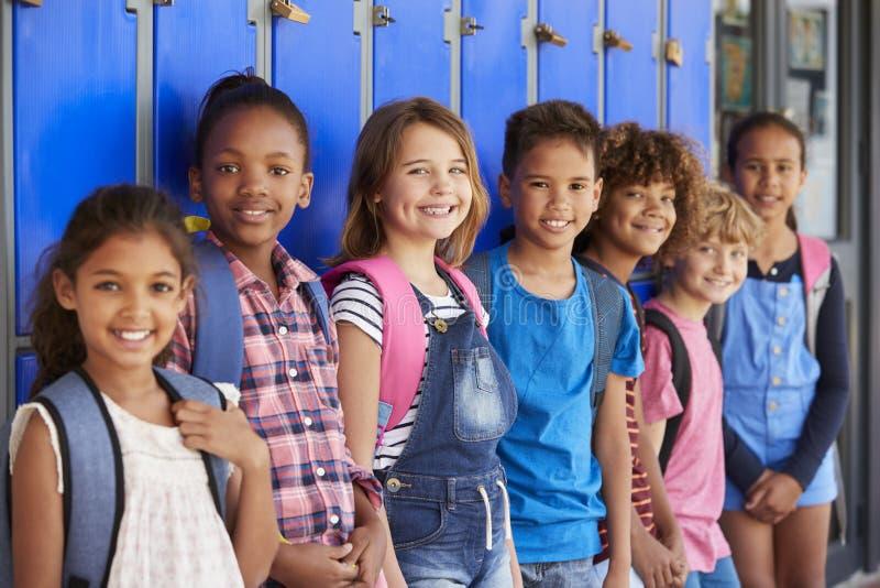 在小学走廊教育在衣物柜前面的孩子 免版税库存照片