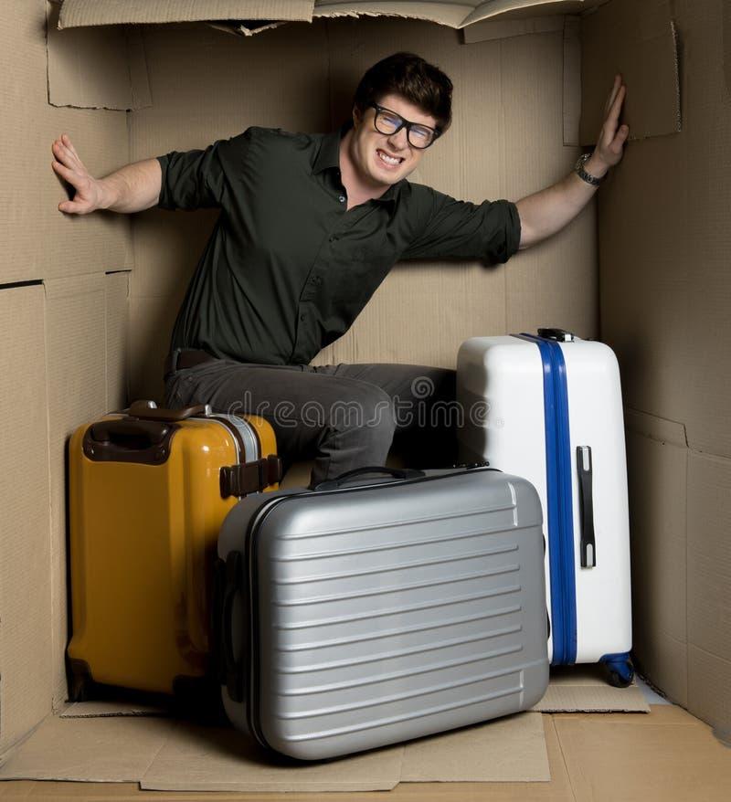 在小室里面的懊恼年轻人感觉难受有行李的 免版税库存照片