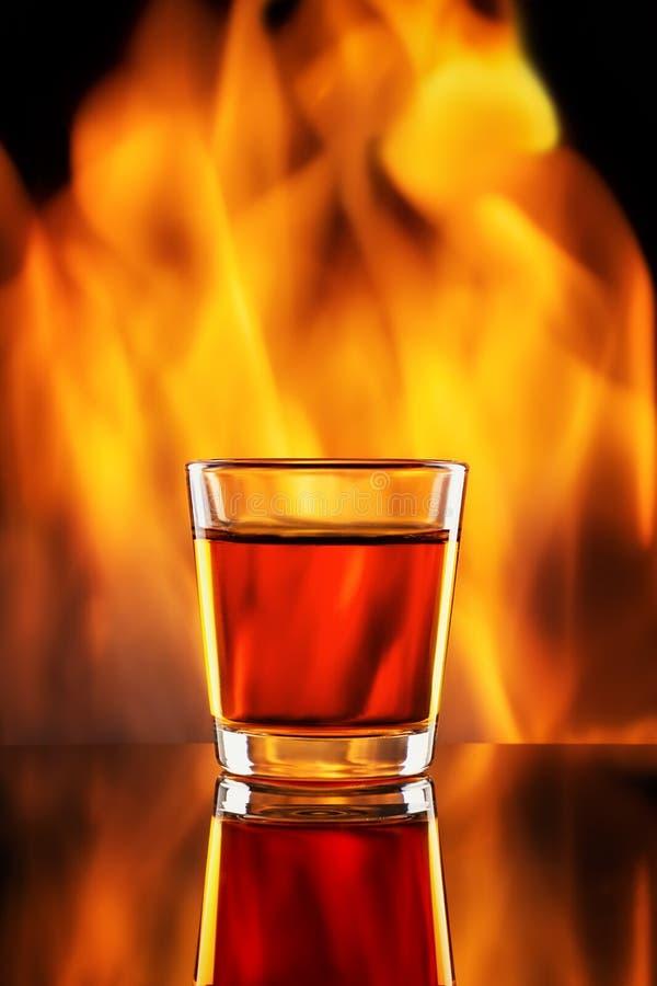 在小小玻璃和火的威士忌酒 免版税图库摄影