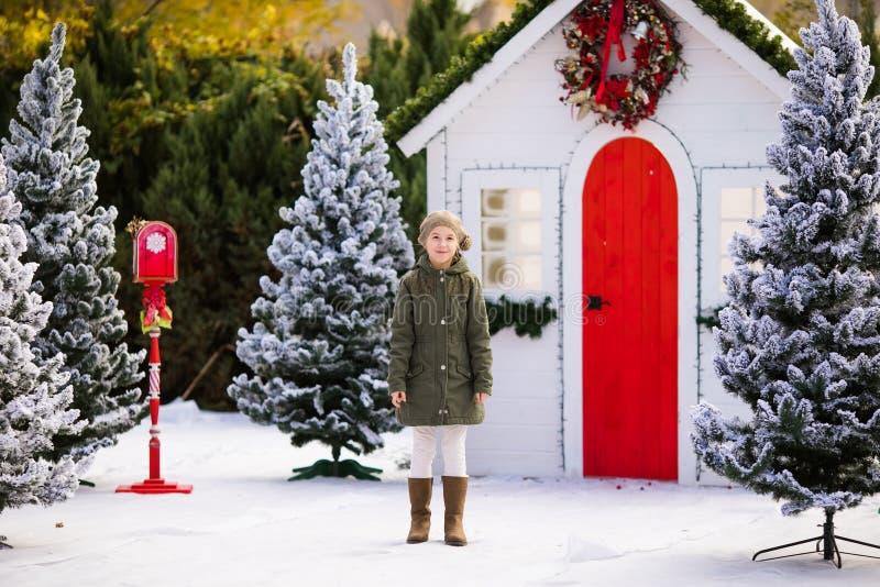 在小屋和积雪的树附近的逗人喜爱的白肤金发的女孩 新年度和圣诞节时间 免版税库存图片
