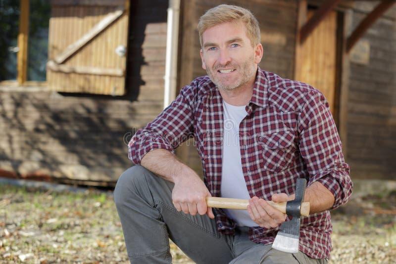 在小屋附近的有胡子的伐木工人 免版税库存图片