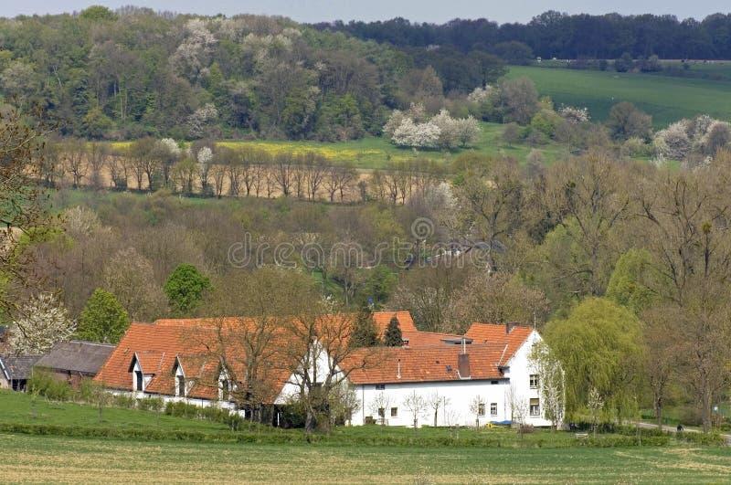 在小山、农场和开花树的全景 库存图片