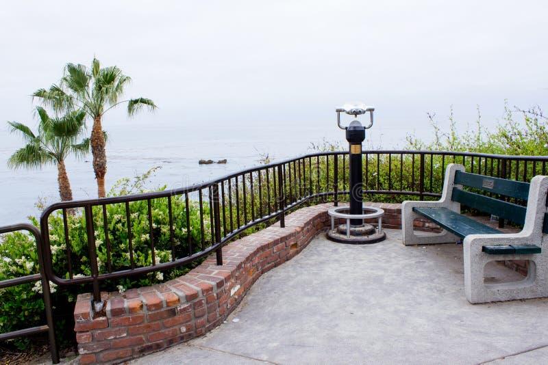 在小山俯视的海洋顶部的弯曲的锻铁和砖篱芭周围的神色点 免版税库存图片