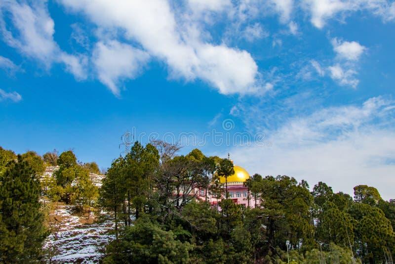 在小山区域的农田的雪下降与树的在白色云彩和天空蔚蓝 免版税库存图片