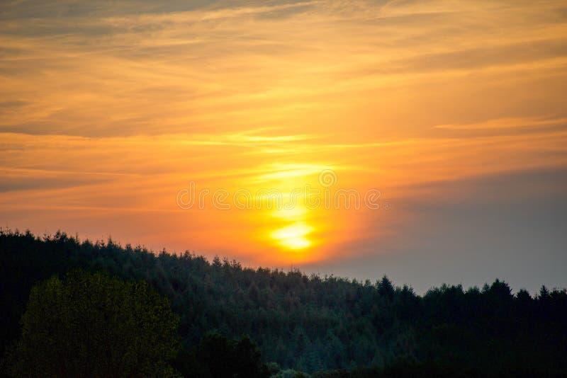 在小山和森林的橙色日落 免版税库存照片