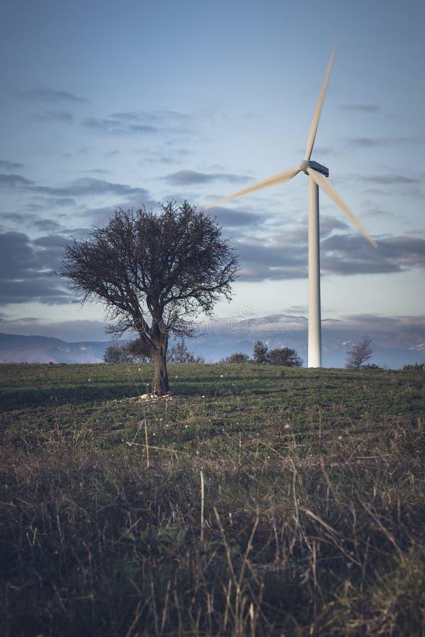 在小山引起干净和能承受的能量在萨莱诺,意大利附近的风轮机 免版税库存图片