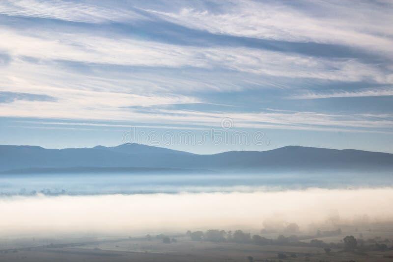 在小山机智围拢的谷的美好的早晨大气 库存图片