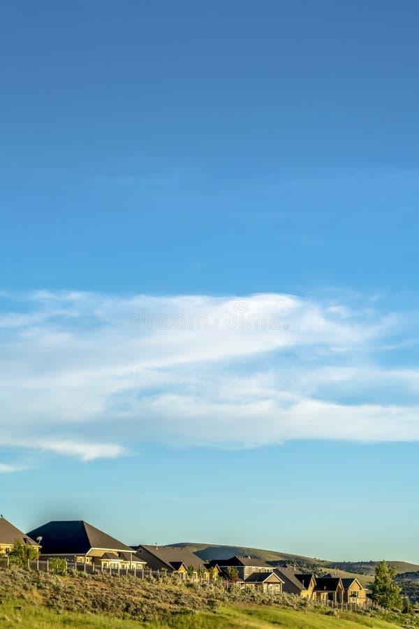 在小山的住所与平安的天空蔚蓝和云彩在头顶上在一好日子 库存图片