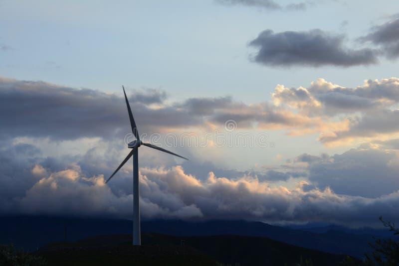 在小山的唯一风力涡轮在美丽的多云天空前面 免版税图库摄影