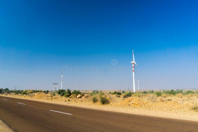 在小山的巨大的现代风车与在后边前面和天空蔚蓝的大厦 库存图片