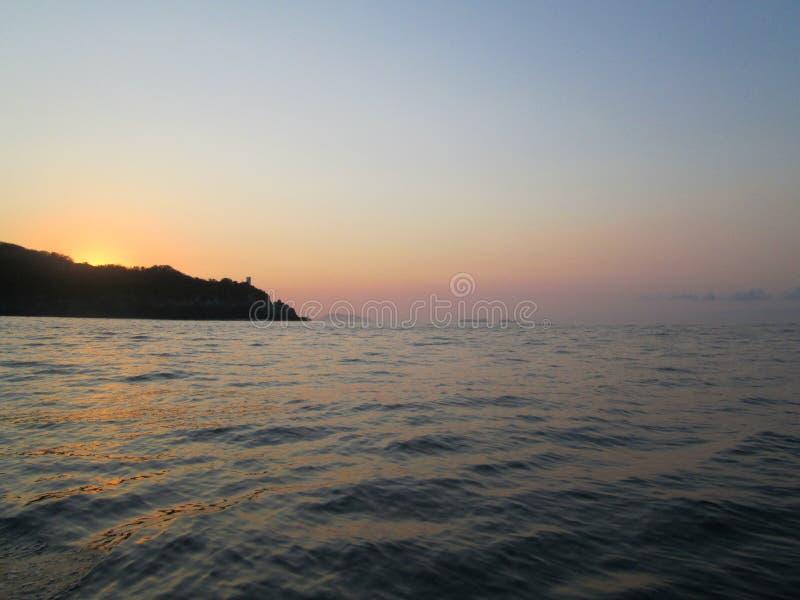 在小山的海洋日出 免版税库存图片