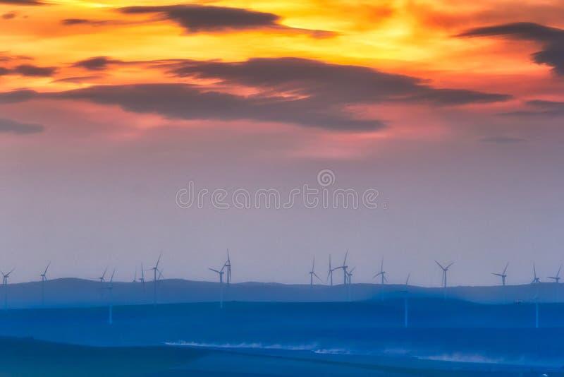 在小山的美好的日落与风轮机 免版税库存图片