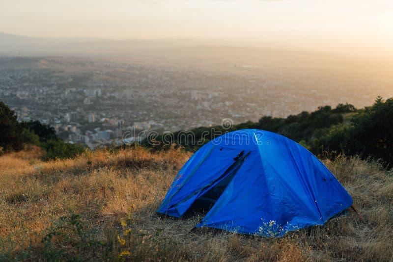 在小山的蓝色帐篷在城市附近 免版税库存照片