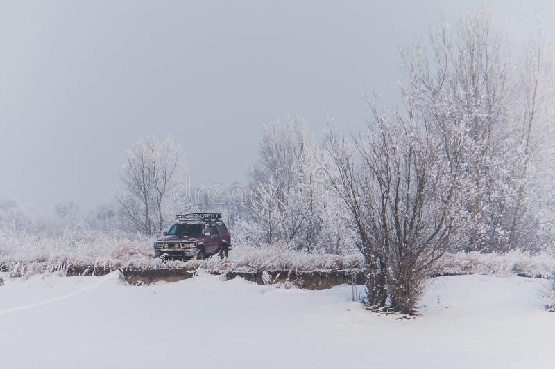 在小山的被放弃的SUV在雪 免版税库存照片