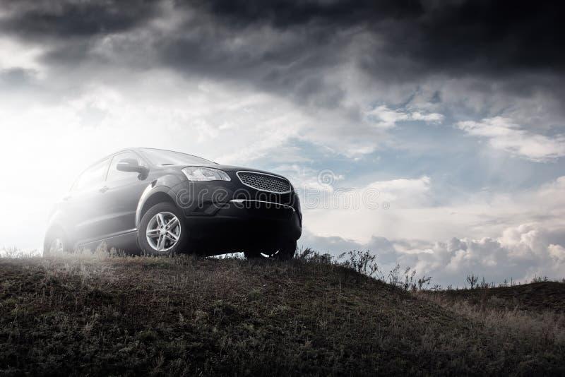 在小山的黑汽车逗留在白天的剧烈的云彩 免版税库存图片