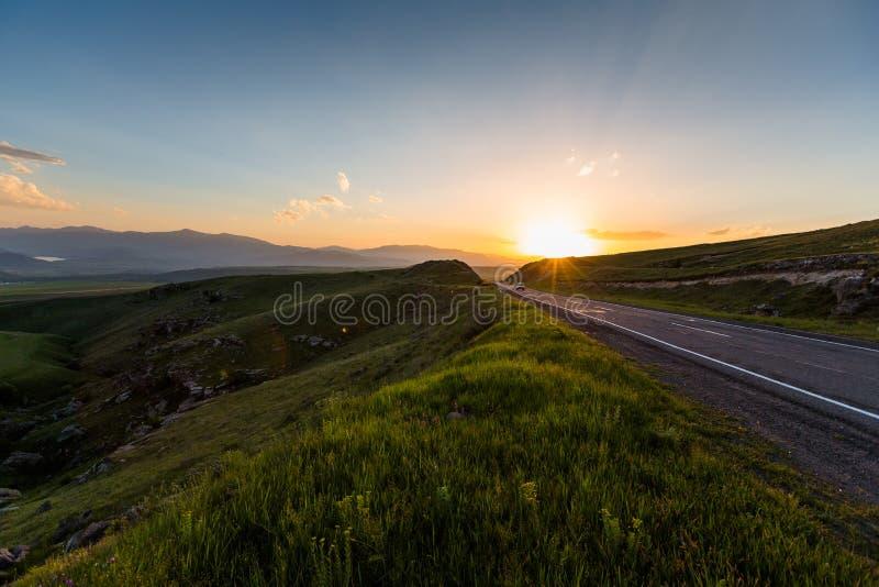 在小山附近的路在日落时间 免版税库存图片