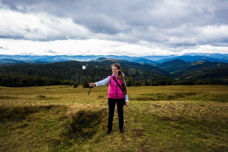 在小山顶部的年轻旅客女孩有山的美丽的景色 库存照片