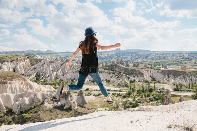 在小山顶部的年轻美丽的旅行女孩在卡帕多细亚,土耳其 她跳  旅行,成功,自由,成就 免版税库存图片