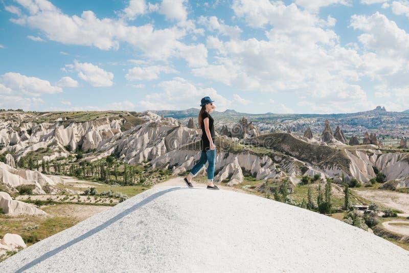 在小山顶部的年轻美丽的旅行女孩在卡帕多细亚,土耳其 旅行,成功,自由,成就 她去 图库摄影