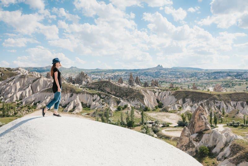 在小山顶部的年轻美丽的旅行女孩在卡帕多细亚,土耳其 旅行,成功,自由,成就 免版税库存图片