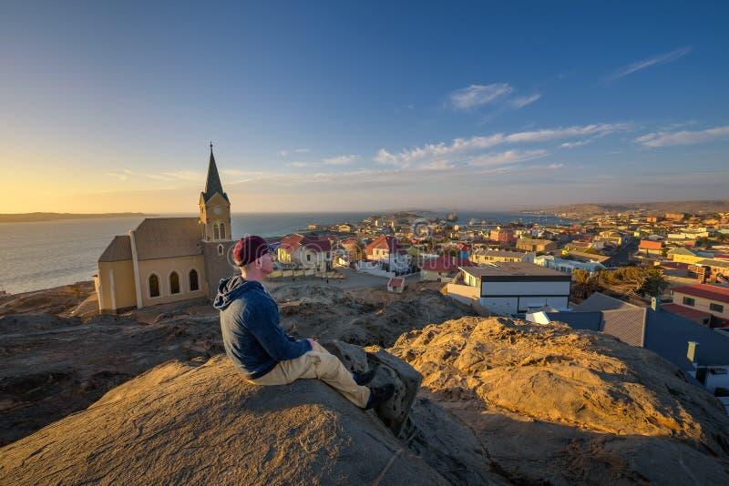 在小山顶部的游人享受吕德里茨看法在纳米比亚在日落 库存照片