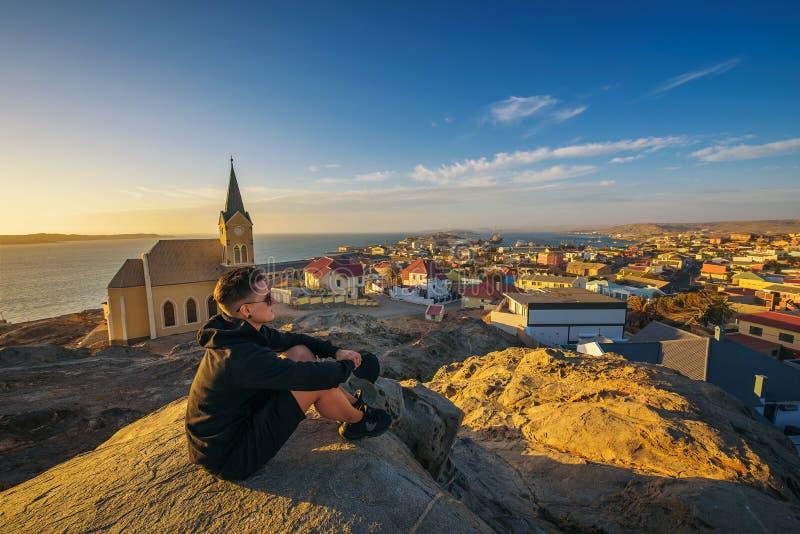 在小山顶部的游人享受吕德里茨看法在纳米比亚在日落 库存图片