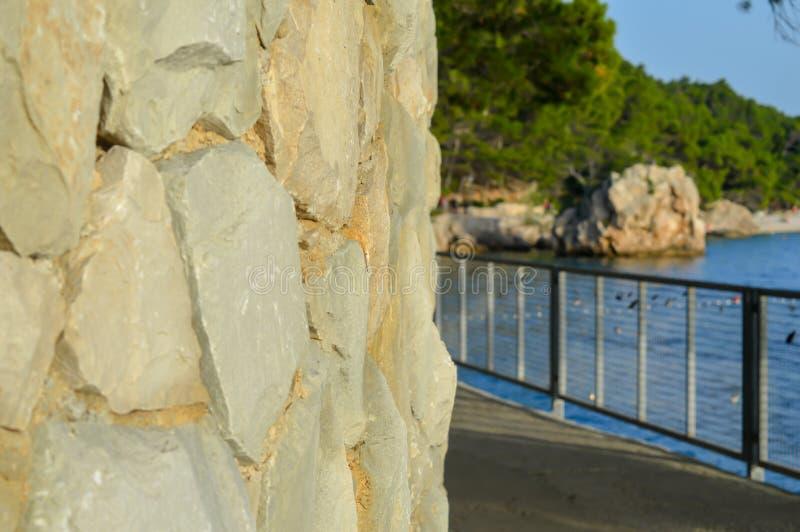 在小岛背景的石墙在蓬塔Rata海滩的在度假圣地Brela 库存图片
