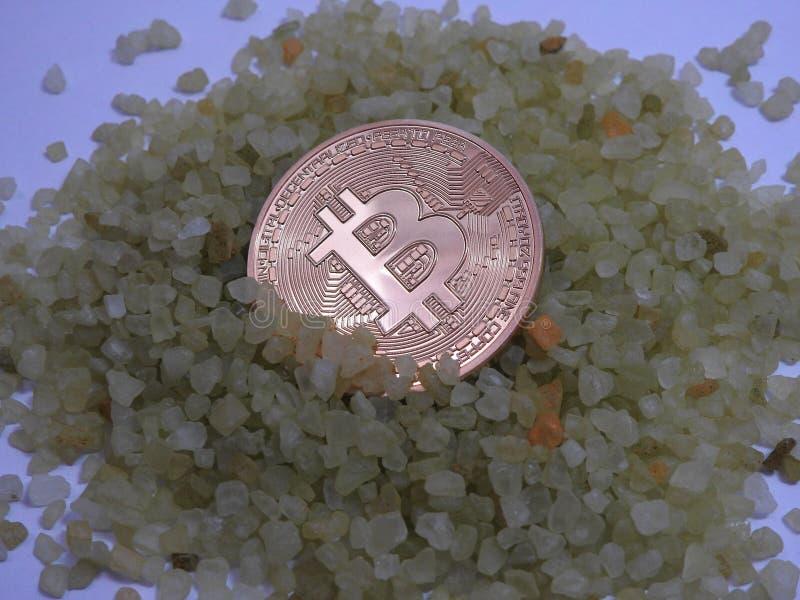 在小岩石的金黄Bitcoin 免版税图库摄影