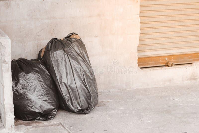 在小径的黑垃圾在小路在大城市,废物,污染 免版税库存图片