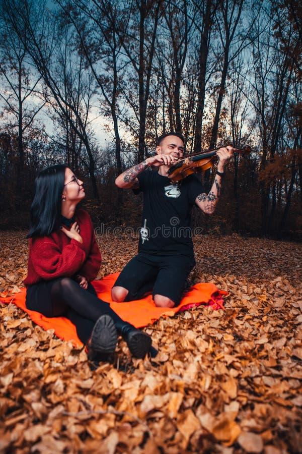 在小提琴的年轻人戏剧和年轻女人坐格子花呢披肩在秋天森林里 图库摄影