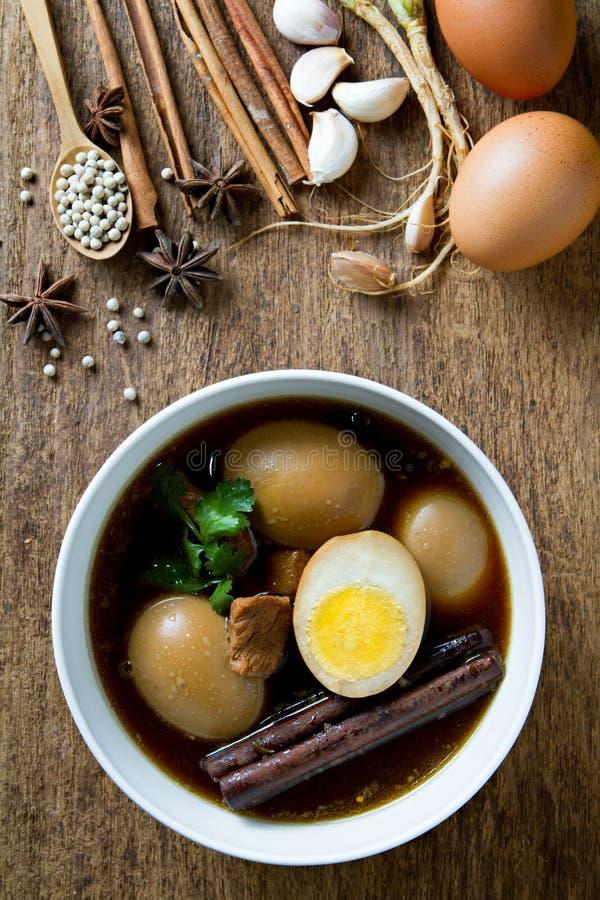 在小汤煮沸的鸡蛋用在木背景的香料 泰国烹调(Kai pa lo) 库存照片