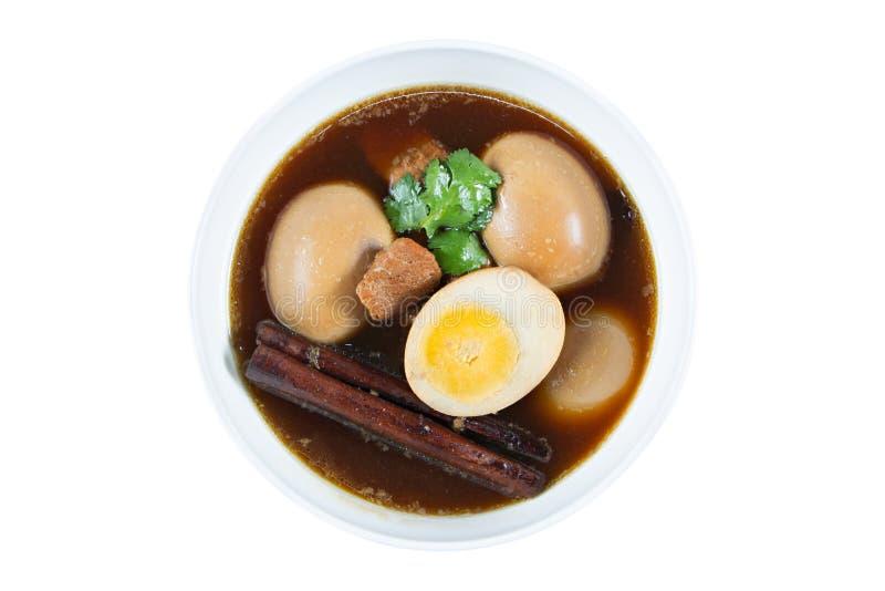 在小汤煮沸的鸡蛋用在白色隔绝的香料 泰国烹调(Kai pa lo) 图库摄影