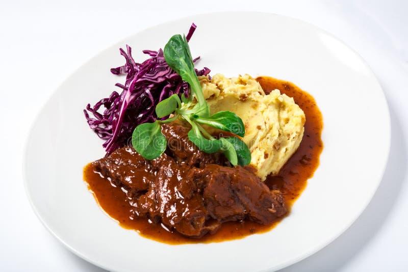 在小汤的小牛肉面颊用土豆和圆白菜,装饰的草本 库存照片