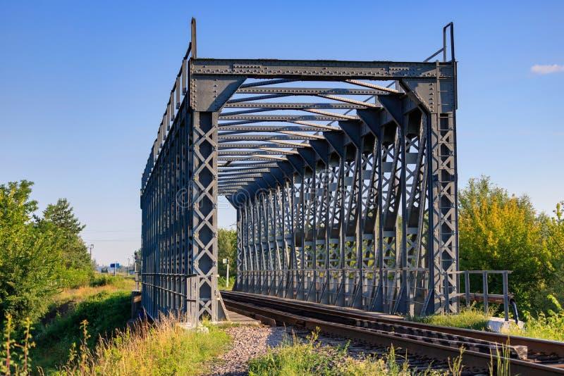 在小河的铁路桥在蓝天背景的乡下和树在晴朗的夏天早晨 苹果覆盖花横向草甸本质星期日结构树 免版税库存照片