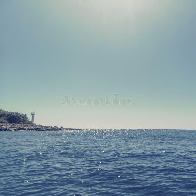 在小海岛天空蔚蓝的小灯塔 免版税库存图片