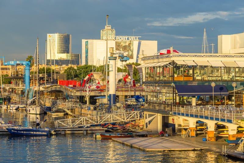 在小游艇船坞停泊的专属游艇在日落,大厦在港口,巴塞罗那,西班牙 免版税图库摄影
