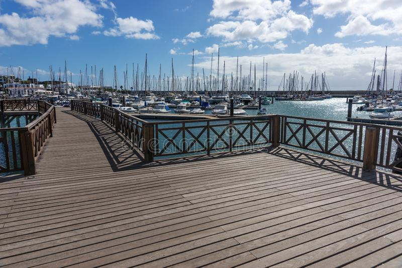 在小游艇船坞卢比孔河小船港口的木桥Playa布朗卡的 兰萨罗特岛 免版税图库摄影