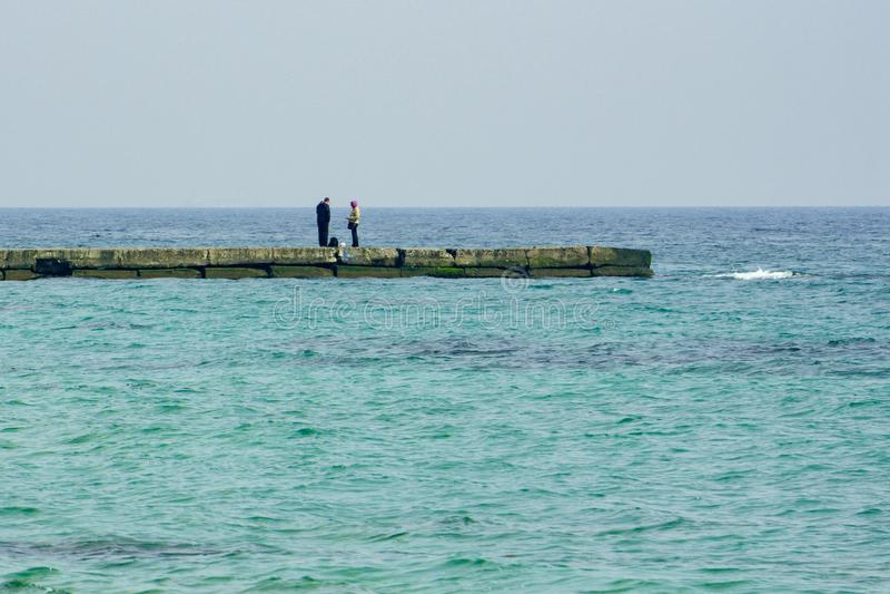 在小游艇船坞的偏僻的已婚夫妇,全景 库存图片