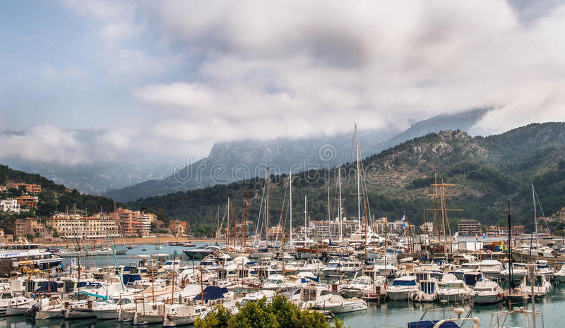 在小游艇船坞的游艇在Port反对山和多云天空的de索勒在马略卡,西班牙 免版税库存照片