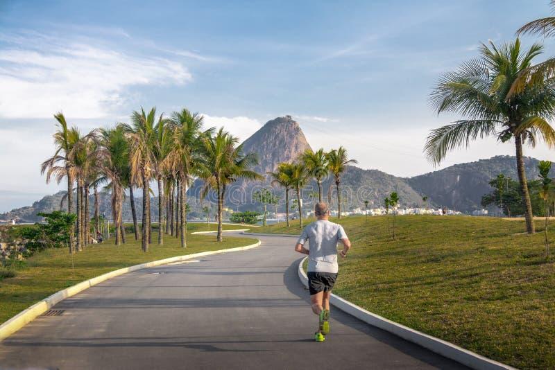 在小游艇船坞da格洛里亚轨道和老虎山山的人赛跑在背景-里约热内卢,巴西 免版税库存照片