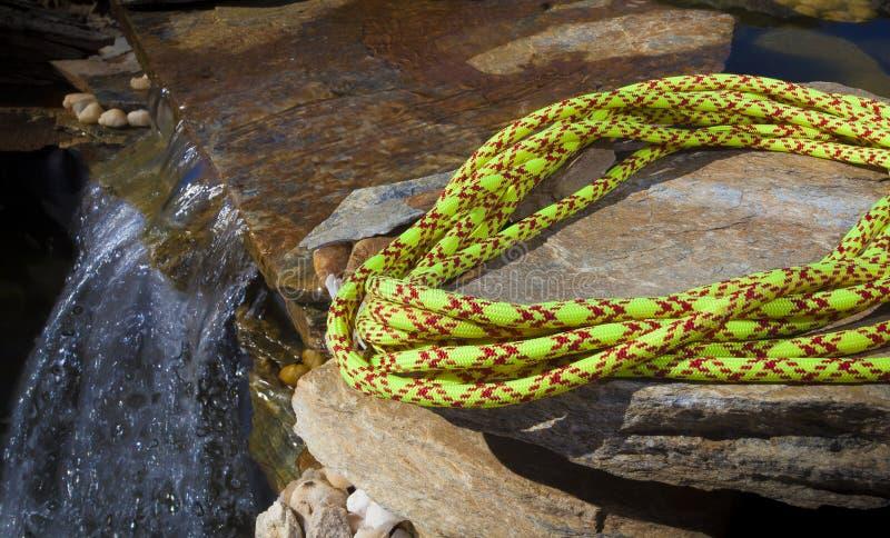 在小瀑布旁边的上升的绳索 免版税库存照片