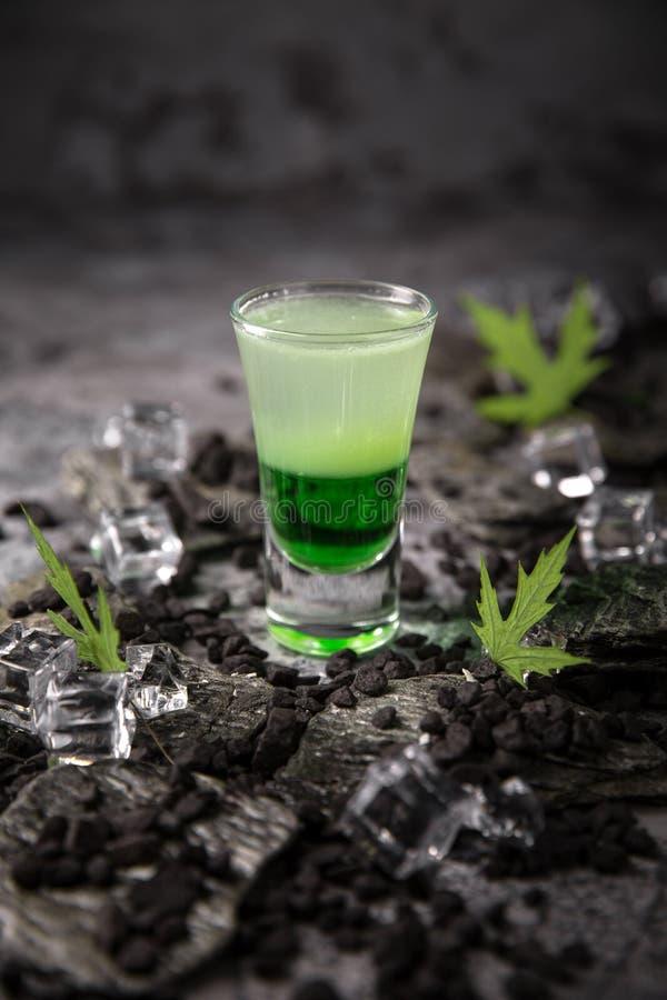 在小玻璃射击者的酒精绿色墨西哥鸡尾酒 从强的伏特加酒、威士忌酒和甜利口酒的冷饮 库存图片