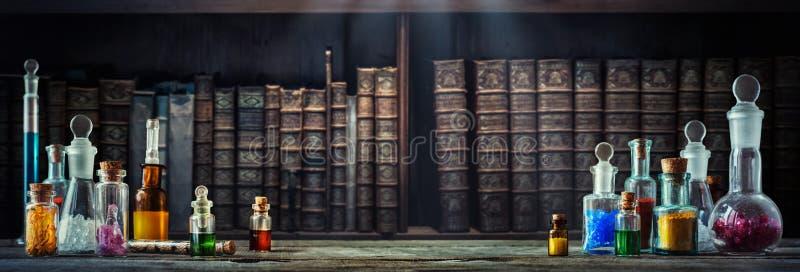 在小瓶的葡萄酒疗程在木书桌和旧书背景 老医疗,化学和药房历史概念 免版税图库摄影