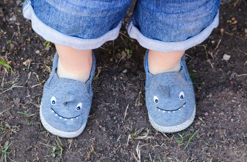 在小男孩站立在土的` s腿的逗人喜爱的鲨鱼鞋子-从上面的看法与他的蓝色牛仔裤底部短缺显示 免版税库存照片