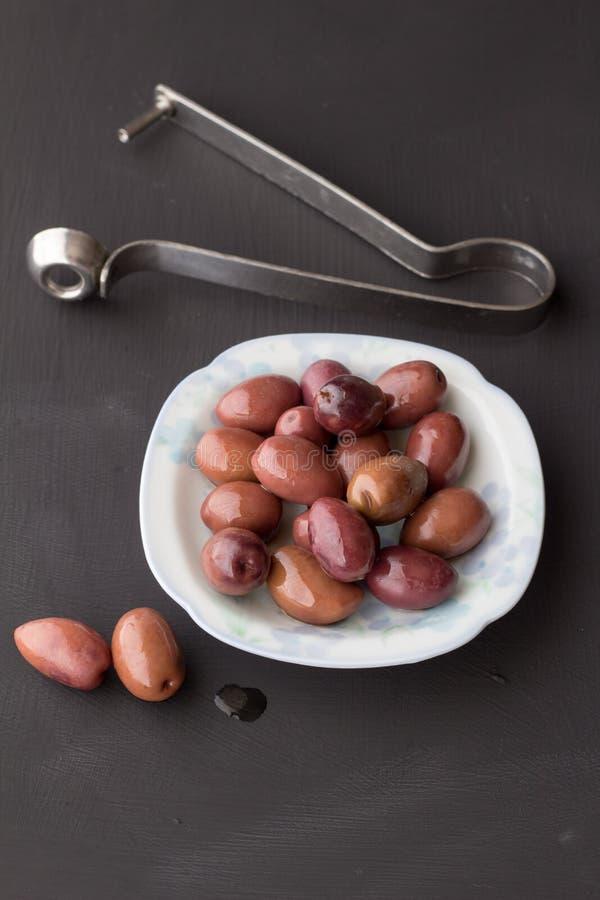 在小白色碗的紫色橄榄有两的在黑粉笔板和不锈钢橄榄色的去核机在背景中 免版税库存照片