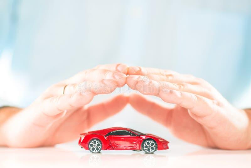 在小红色微型汽车上的男性商人手 背景汽车概念保险查出在白色 免版税库存图片