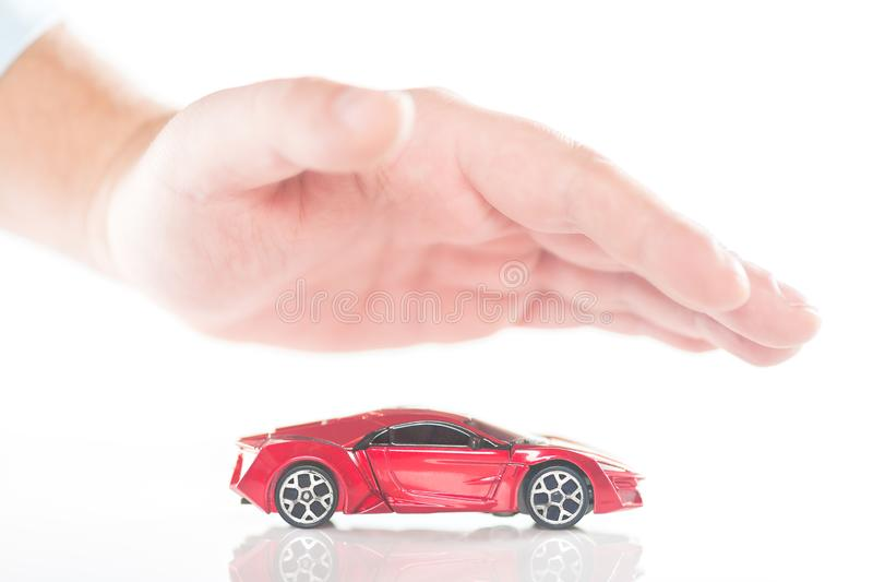 在小红色玩具微型汽车上的男性商人手 汽车保险和保护概念 库存图片
