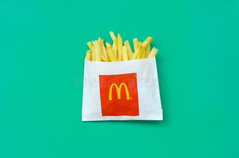 在小纸袋的麦克唐纳薯条在鲜绿色的背景 免版税库存图片