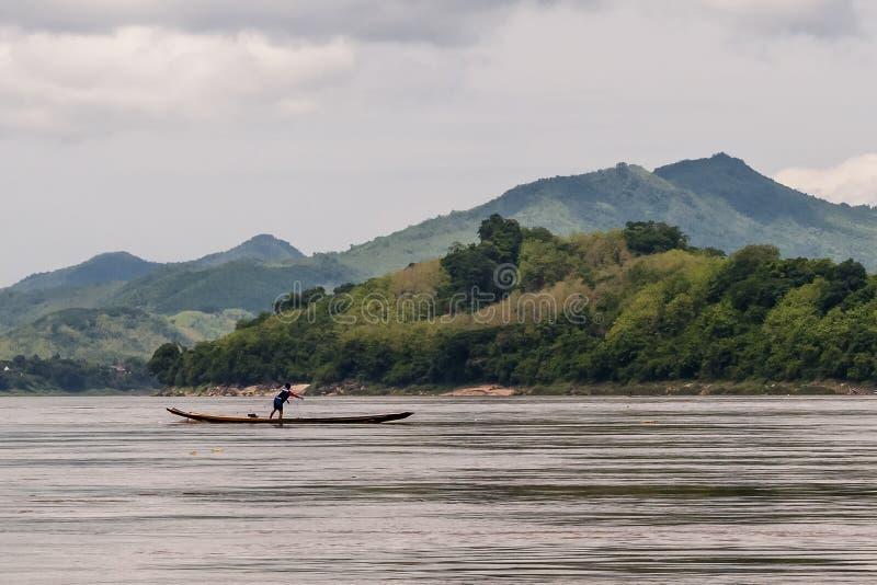 在小船保持平衡的渔夫发射在湄公河,琅勃拉邦,老挝的网 库存照片